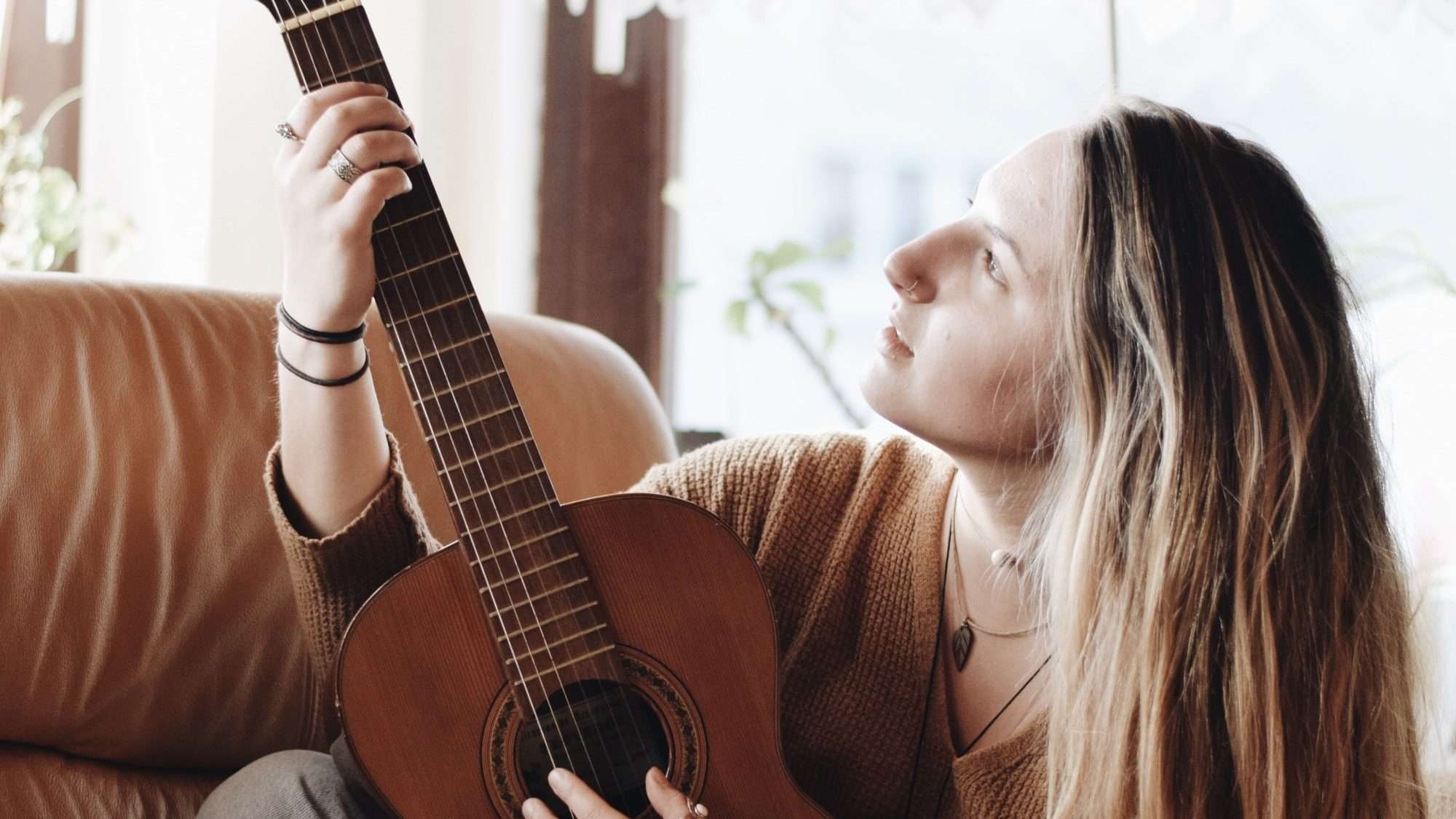 Woman playing classical guitar next to a window