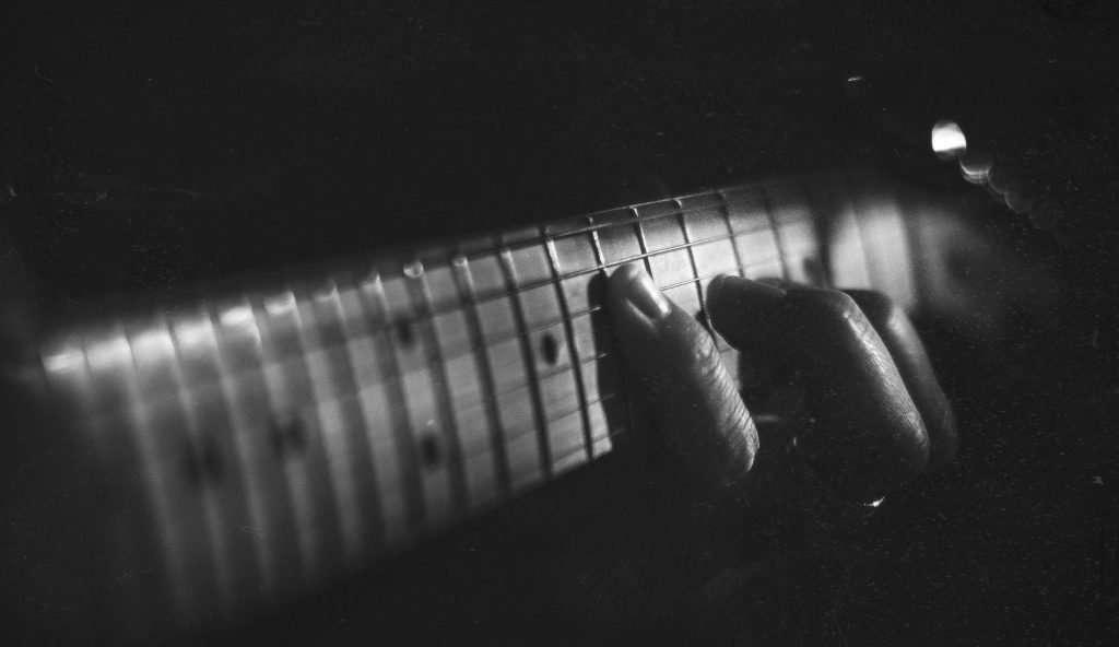 Hand playing guitar fretboard
