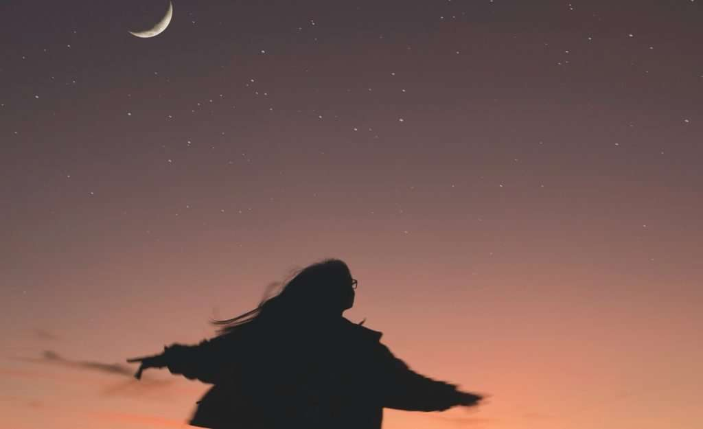 Woman overjoyed with outstretched arms looking at the night sky